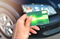 Mano della donna che tiene la carta di credito verde usando per comprare una nuova automobile Affare automatico, concetto di vend immagini stock