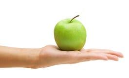 Mano della donna che tiene mela verde. Fotografia Stock
