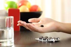 Mano della donna che tiene una pillola del complesso della vitamina Fotografia Stock Libera da Diritti