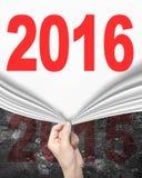 Mano della donna che tira nuova tenda 2016 che copre vecchia parete 2015 Immagine Stock