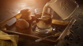 Mano della donna che versa latte fresco nel vetro con caffè nero archivi video