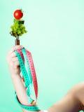 Mano della donna con alimento vegetariano e nastri adesivi di misurazione Immagini Stock