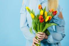 Mano della donna con il mazzo giallo rosso dei tulipani Immagini Stock