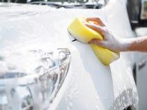 Mano della donna con l'automobile gialla di lavaggio della spugna fotografia stock