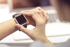Mano della donna con l'orologio astuto sul polso, l'orologio portabile ed il computer portatile del computer di tecnologia per la fotografia stock