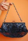 Mano della donna con la borsa del partito Immagine Stock