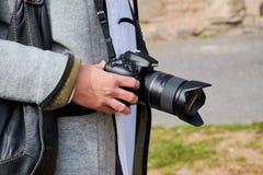 Mano della donna con la macchina fotografica di Nikon e la lente del tamron immagini stock