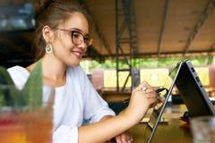 Mano della donna della corsa mista delle free lance che indica con lo stilo sullo schermo convertibile del computer portatile nel fotografie stock