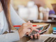 Mano della donna del primo piano che lavora al calcolatore con la matita rossa Fotografie Stock Libere da Diritti