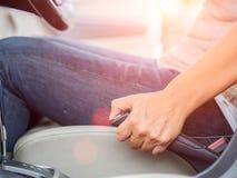 Mano della donna del primo piano che tira il freno a mano dell'automobile e che conduce un'automobile fotografia stock libera da diritti