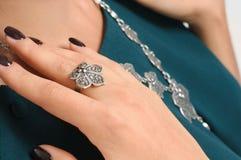 Mano della donna del primo piano con l'anello sul dito e sulla collana sul backgrou Immagini Stock Libere da Diritti