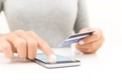 mano della donna del primo piano facendo uso del telefono e dell'acquisto della carta di credito Fotografie Stock Libere da Diritti