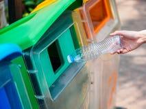 Mano della donna del ritratto del primo piano che getta bottiglia di acqua di plastica vuota Immagine Stock