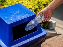 Mano della donna del ritratto del primo piano che getta bottiglia di acqua di plastica vuota Fotografia Stock Libera da Diritti