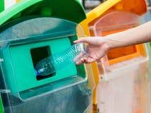 Mano della donna del ritratto del primo piano che getta bottiglia di acqua di plastica vuota Immagini Stock