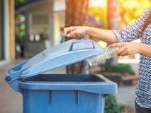 Mano della donna del ritratto del primo piano che getta bottiglia di acqua di plastica vuota Fotografie Stock Libere da Diritti