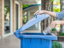 Mano della donna del ritratto del primo piano che getta bottiglia di acqua di plastica vuota nel recipiente di riciclaggio Fotografia Stock Libera da Diritti