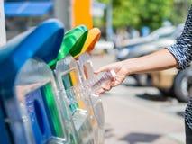 Mano della donna del ritratto del primo piano che getta bottiglia di acqua di plastica vuota nel recipiente di riciclaggio Immagini Stock
