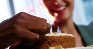 Mano della donna di affari che accende le candele sul dolce con il collega stock footage