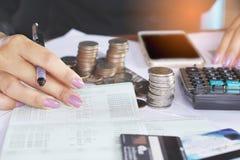 Mano della donna di affari che analizza sul libro contabile, con il mucchio delle monete, Fotografia Stock Libera da Diritti