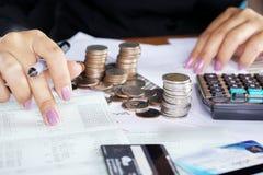 Mano della donna di affari che conta sul conto di risparmio con la pila di monete Fotografie Stock