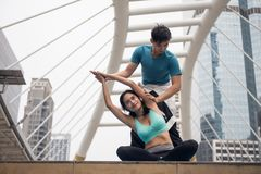 mano della donna di allungamento dell'istruttore di yoga in città Fotografia Stock