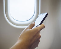 Mano della donna facendo uso del telefono cellulare in aeroplano Immagini Stock