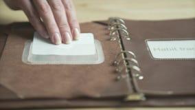 Mano della donna facendo uso dell'inseguitore quotidiano elegante di abitudine del libro del blocco note del pianificatore di cas archivi video