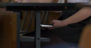 Mano della donna facendo uso di uno Smart Phone sotto una tavola di legno La donna usa Internet sul vostro telefono durante l'esa archivi video