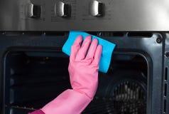 Mano della donna in guanto protettivo con il ki del forno di pulizia dello straccio a casa immagine stock libera da diritti