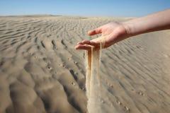 Mano della donna nella sabbia Fotografie Stock
