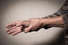 Mano della donna senior che massaggia polso immagine stock