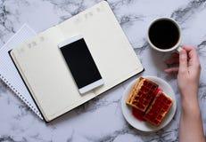 Mano della donna, tazza di caff?, giorno di pianificazione, pranzo di lavoro e smartphone immagini stock