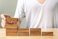 Mano della femmina che sistema blocco di legno che impila come scala di punto Busi Fotografia Stock Libera da Diritti