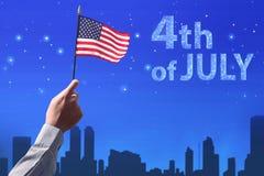 Mano della gente che tiene la bandiera di U.S.A. che celebra il quarto luglio Fotografie Stock Libere da Diritti