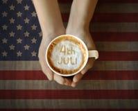 Mano della gente che tiene tazza di coffe con il quarto del messaggio di luglio Fotografie Stock