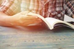 Mano della gente, dell'apertura dello studente e del libro di testo della lettura sulla tavola di legno con lo spazio della copia Immagini Stock