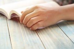 Mano della gente, dell'apertura dello studente e del libro di testo della lettura sulla tavola di legno con lo spazio della copia Immagini Stock Libere da Diritti
