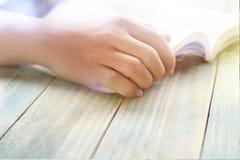 Mano della gente, dell'apertura dello studente e del libro di testo della lettura sulla tavola di legno con lo spazio della copia Fotografia Stock