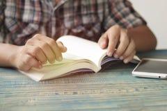 Mano della gente, dell'apertura dello studente e del libro di testo della lettura sulla tavola di legno con lo spazio della copia Immagine Stock