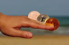 Mano della giovane donna con la moneta fisica del pezzo nella spiaggia, concetto della moneta del pezzo, commercio elettronico Fotografie Stock Libere da Diritti
