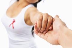 Mano della holding della donna per supportare causa del AIDS Immagine Stock
