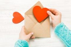 Mano della lettera di amore di scrittura della ragazza il giorno dei biglietti di S. Valentino del san Handma Immagine Stock