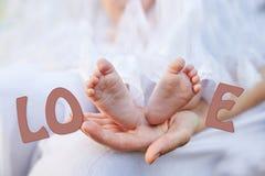 Mano della madre che tiene i piccoli piedi del bambino immagini stock libere da diritti