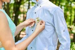 Mano della moglie sulla camicia del marito Fotografia Stock
