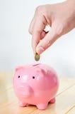 Mano della moneta mettente maschio nel porcellino salvadanaio rosa Fotografia Stock Libera da Diritti