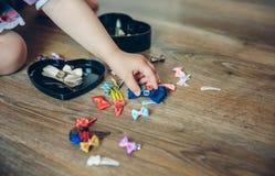Mano della neonata che gioca con le clip di capelli in Fotografia Stock