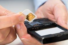 Mano della persona con la carta SIM ed il telefono cellulare Immagini Stock