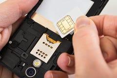 Mano della persona con la carta SIM ed il telefono cellulare Fotografie Stock