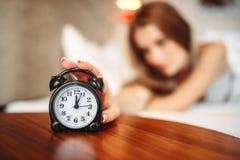 Mano della persona femminile sulla sveglia, svegliante Fotografia Stock Libera da Diritti